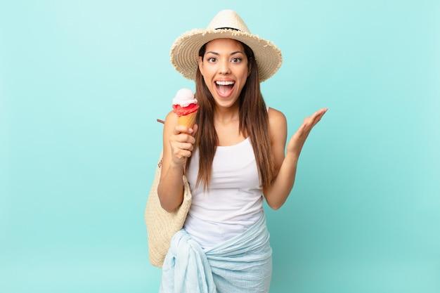 Młoda latynoska kobieta czuje się szczęśliwa i zdumiona czymś niewiarygodnym i trzyma lody. koncepcja suma