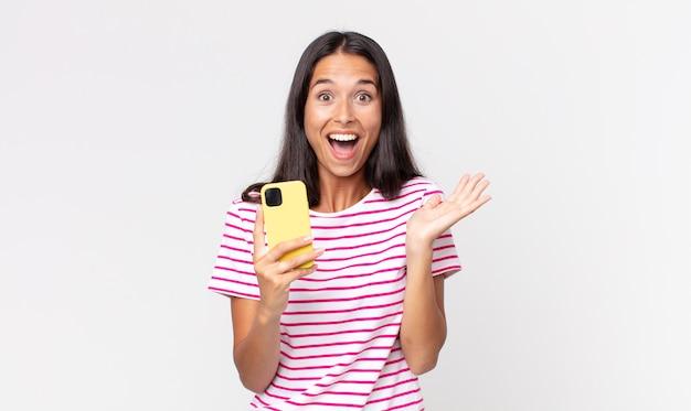 Młoda latynoska kobieta czuje się szczęśliwa i zdumiona czymś niewiarygodnym i trzyma smartfon
