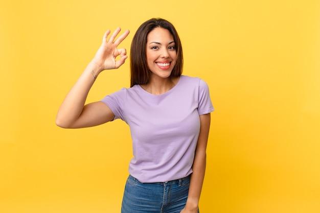 Młoda latynoska kobieta czuje się szczęśliwa, okazując aprobatę dobrym gestem