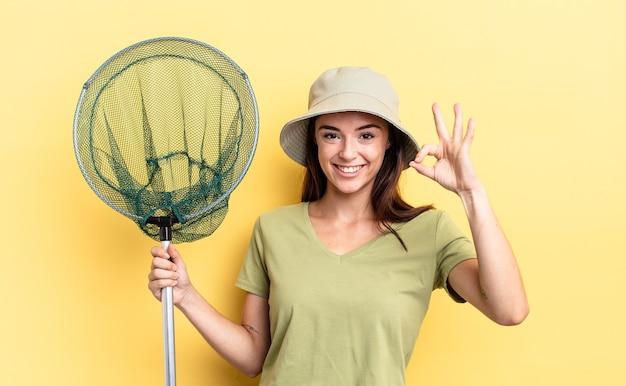 Młoda latynoska kobieta czuje się szczęśliwa, okazując aprobatę z koncepcją sieci rybackiej w porządku gest