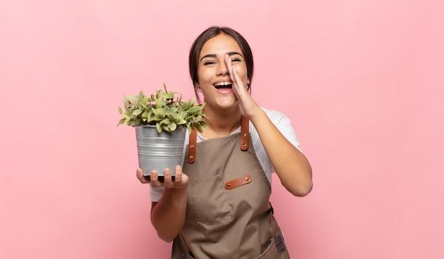 Młoda latynoska kobieta czuje się szczęśliwa, podekscytowana i pozytywna, krzyczy głośno z rękami przy ustach i woła