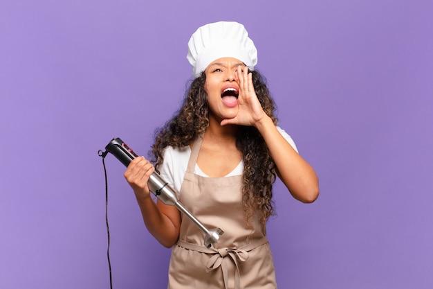 Młoda latynoska kobieta czuje się szczęśliwa, podekscytowana i pozytywna, wydając wielki okrzyk z rękami przy ustach, wołając. koncepcja szefa kuchni