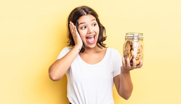 Młoda latynoska kobieta czuje się szczęśliwa, podekscytowana i zaskoczona. koncepcja butelki ciasteczek