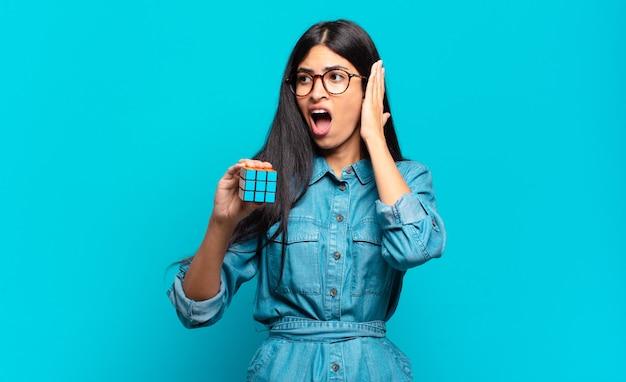 Młoda latynoska kobieta czuje się szczęśliwa, podekscytowana i zaskoczona, patrząc w bok z obiema rękami na twarzy. koncepcja problemu inteligencji