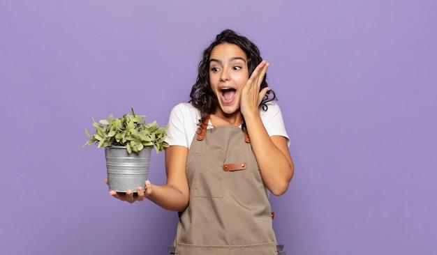 Młoda latynoska kobieta czuje się szczęśliwa, podekscytowana i zaskoczona, patrząc w bok z obiema rękami na twarzy