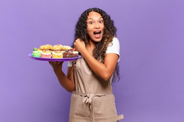 Młoda latynoska kobieta czuje się szczęśliwa, pozytywna i odnosząca sukcesy, zmotywowana, gdy mierzy się z wyzwaniem lub świętuje dobre wyniki. koncepcja gotowania ciast