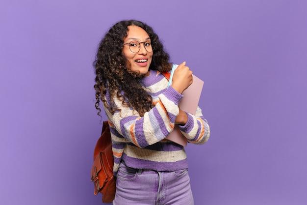 Młoda latynoska kobieta czuje się szczęśliwa, pozytywna i odnosząca sukcesy, zmotywowana, gdy mierzy się z wyzwaniem lub świętuje dobre wyniki. koncepcja studenta