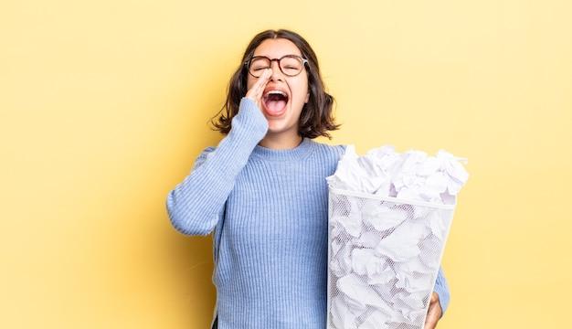Młoda latynoska kobieta czuje się szczęśliwa, wydając wielki okrzyk z rękami przy ustach, nie powiodła się koncepcja śmieci