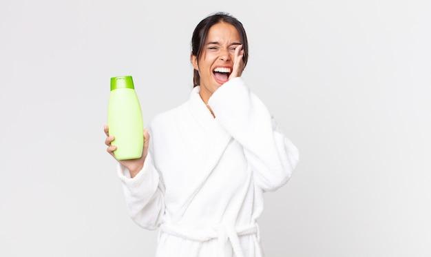 Młoda latynoska kobieta czuje się szczęśliwa, wydając wielki okrzyk z rękami przy ustach, ubrana w szlafrok i trzymająca szampon
