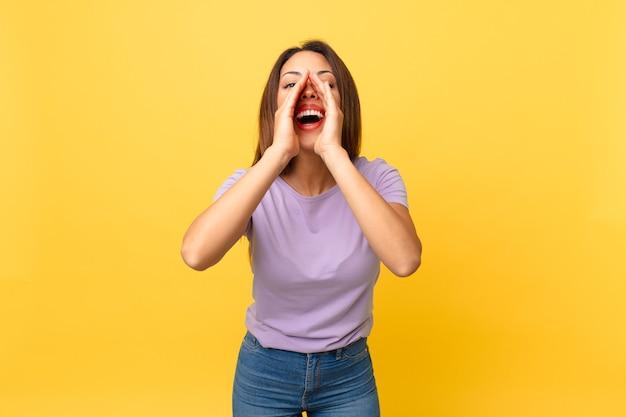 Młoda latynoska kobieta czuje się szczęśliwa, wydając wielki okrzyk z rękami przy ustach