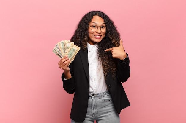 Młoda latynoska kobieta czuje się szczęśliwa, zaskoczona i dumna, wskazując na siebie z podekscytowanym, zdumionym spojrzeniem. koncepcja banknotów dolarowych