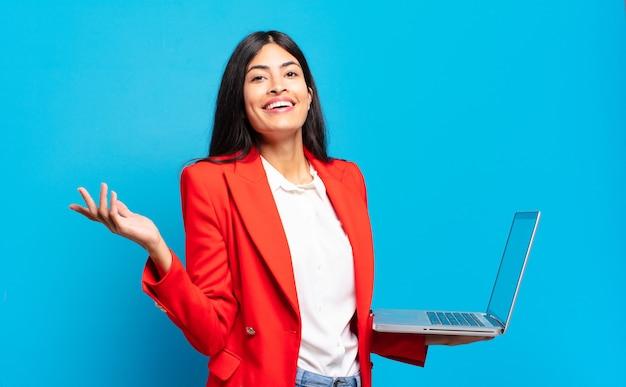 Młoda latynoska kobieta czuje się szczęśliwa, zaskoczona i pogodna, uśmiechnięta z pozytywnym nastawieniem, realizująca rozwiązanie lub pomysł. koncepcja laptopa