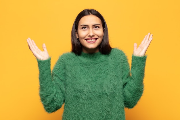 Młoda latynoska kobieta czuje się szczęśliwa, zdumiona, szczęśliwa i zaskoczona, świętując zwycięstwo z obiema rękami w górze