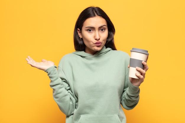 Młoda latynoska kobieta czuje się zakłopotana i zdezorientowana, wątpi, waży lub wybiera różne opcje ze śmiesznym wyrazem twarzy