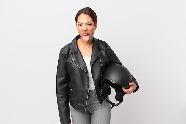 Młoda latynoska kobieta czuje się zdegustowana i zirytowana i wymawia język. koncepcja motocyklisty