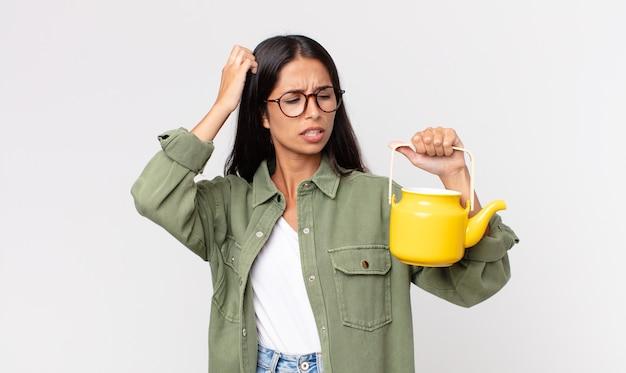 Młoda latynoska kobieta czuje się zdezorientowana i zdezorientowana, drapiąc się po głowie i trzymając dzbanek do herbaty