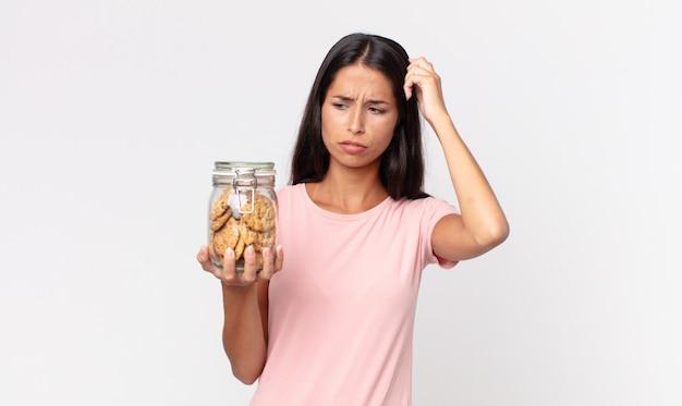 Młoda latynoska kobieta czuje się zdezorientowana i zdezorientowana, drapiąc się po głowie i trzymając szklaną butelkę po ciastkach