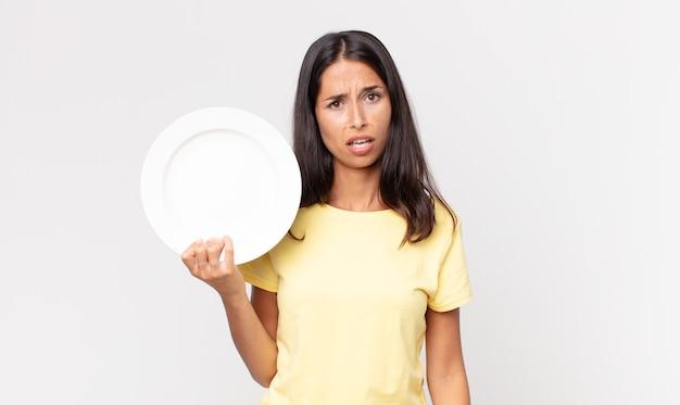 Młoda latynoska kobieta czuje się zdezorientowana i zdezorientowana i trzyma pusty talerz