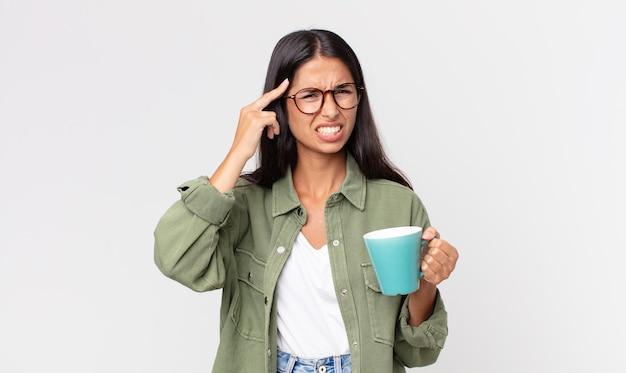 Młoda latynoska kobieta czuje się zdezorientowana i zdezorientowana, pokazując, że jesteś szalony i trzymasz kubek z kawą