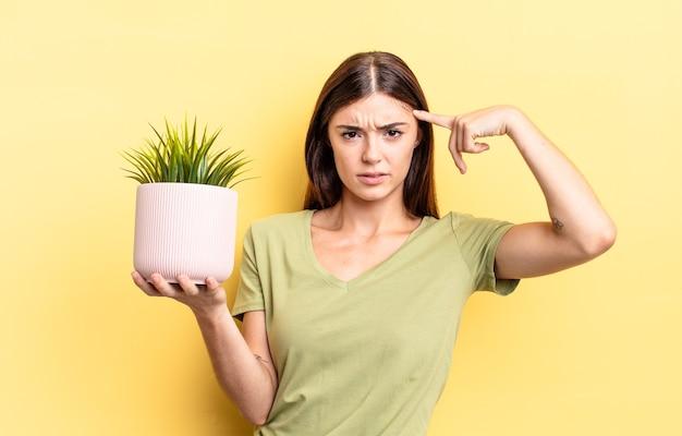 Młoda latynoska kobieta czuje się zdezorientowana i zdezorientowana, pokazując, że jesteś szalony. koncepcja doniczki