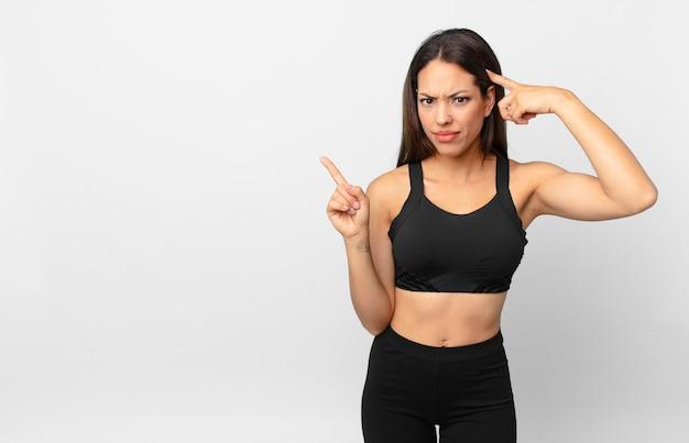 Młoda latynoska kobieta czuje się zdezorientowana i zdezorientowana, pokazując, że jesteś szalony. koncepcja fitness