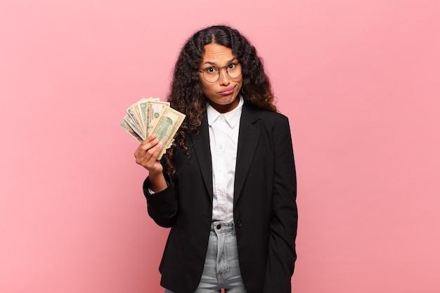 Młoda latynoska kobieta czuje się zdziwiona i zdezorientowana, z głupim, oszołomionym wyrazem twarzy, patrząc na coś nieoczekiwanego. koncepcja banknotów dolara