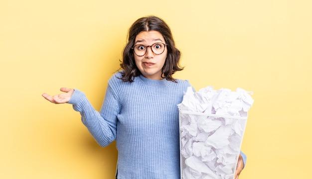 Młoda latynoska kobieta czuje się zdziwiona, zdezorientowana i wątpi w nieudaną koncepcję śmieci