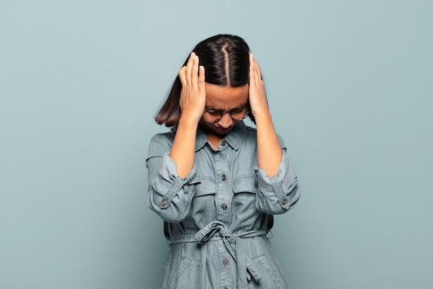 Młoda latynoska kobieta czuje się zestresowana i sfrustrowana, podnosi ręce do głowy, czuje się zmęczona, nieszczęśliwa i ma migrenę