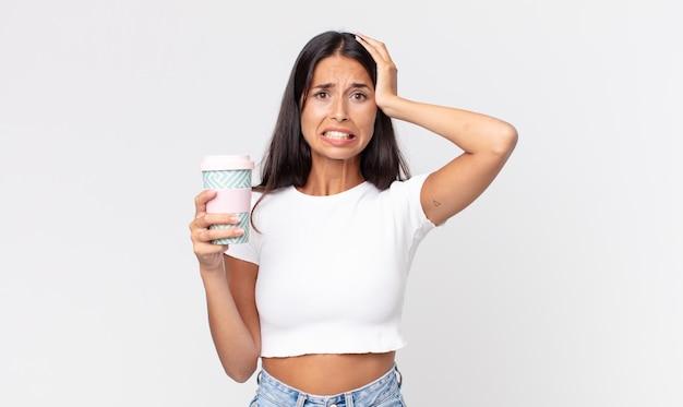 Młoda latynoska kobieta czuje się zestresowana, niespokojna lub przestraszona, z rękami na głowie i trzymającą pojemnik na kawę na wynos