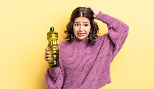Młoda latynoska kobieta czuje się zestresowana, niespokojna lub przestraszona, z rękami na głowie. koncepcja oliwy z oliwek