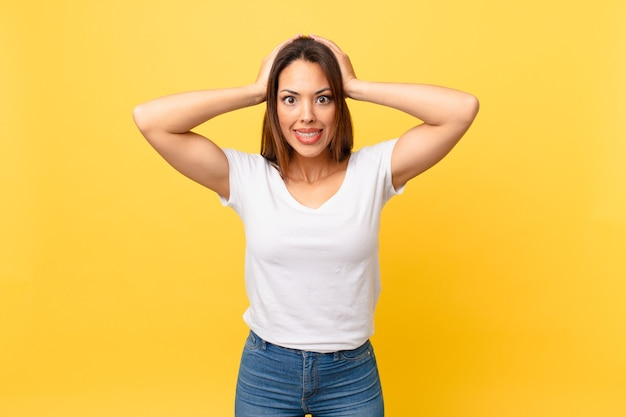 Młoda latynoska kobieta czuje się zestresowana, niespokojna lub przestraszona, z rękami na głowie