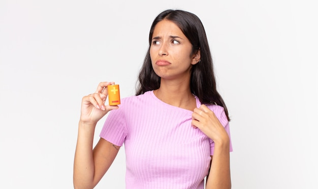 Młoda latynoska kobieta czuje się zestresowana, niespokojna, zmęczona i sfrustrowana i trzyma baterie