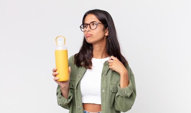 Młoda latynoska kobieta czuje się zestresowana, niespokojna, zmęczona i sfrustrowana i trzyma termos z kawą