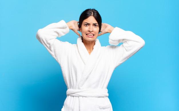 Młoda latynoska kobieta czuje się zestresowana, zmartwiona, niespokojna lub przestraszona, z rękami na głowie, panikuje z powodu błędu