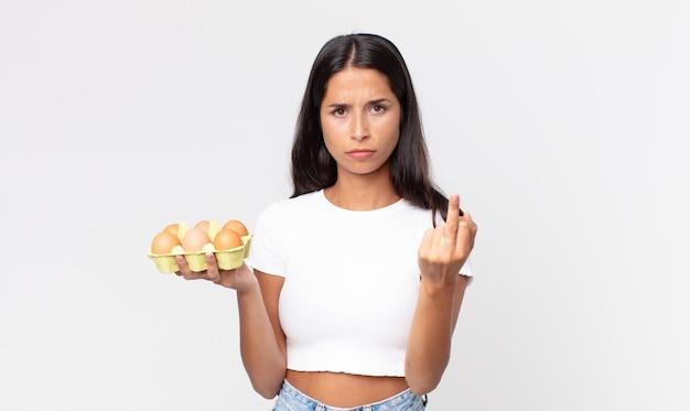 Młoda latynoska kobieta czuje się zła, zirytowana, buntownicza i agresywna i trzyma pudełko z jajkami