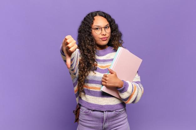 Młoda latynoska kobieta czuje się zła, zła, zirytowana, rozczarowana lub niezadowolona, pokazując kciuki w dół z poważnym spojrzeniem. koncepcja studenta