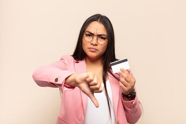 Młoda latynoska kobieta czuje się zła, zła, zirytowana, rozczarowana lub niezadowolona, pokazując kciuki w dół z poważnym spojrzeniem
