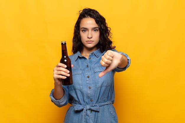Młoda latynoska kobieta czuje się zła, zła, zirytowana, rozczarowana lub niezadowolona, pokazuje kciuki w dół z poważnym spojrzeniem