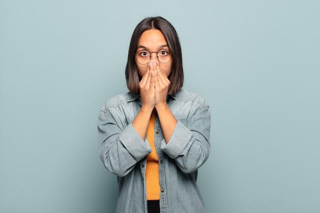 Młoda latynoska kobieta czuje się zmartwiona, zdenerwowana i przestraszona, zakrywa usta rękami, wygląda na zaniepokojoną i popsuła