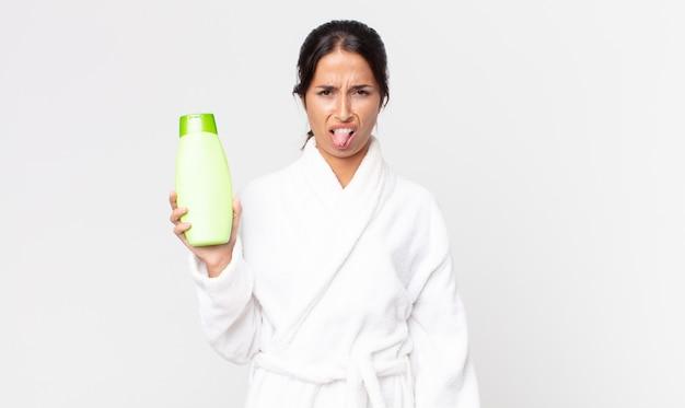 Młoda latynoska kobieta czuje się zniesmaczona i zirytowana, wyciągając język w szlafroku i trzymając szampon