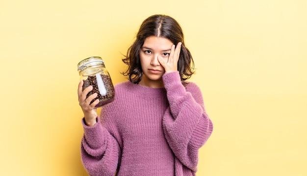 Młoda latynoska kobieta czuje się znudzona, sfrustrowana i senna po męczącym dniu. koncepcja ziaren kawy
