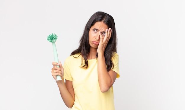 Młoda latynoska kobieta czuje się znudzona, sfrustrowana i senna po męczącym i trzymającym w ręku pędzel do mycia naczyń
