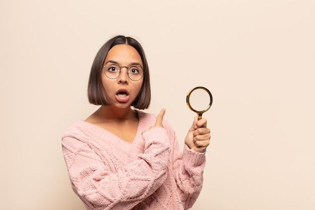 Młoda latynoska kobieta czuje się zszokowana i zaskoczona, wskazując na skopiowanie miejsca z boku ze zdumionym spojrzeniem z otwartymi ustami