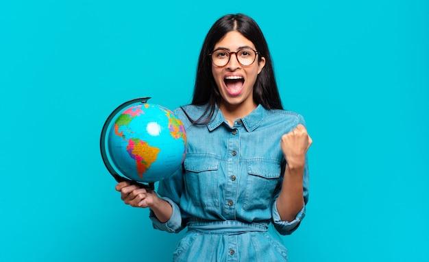 Młoda latynoska kobieta czuje się zszokowana, podekscytowana i szczęśliwa, śmiejąc się i świętując sukces, mówiąc wow!. koncepcja planety ziemi