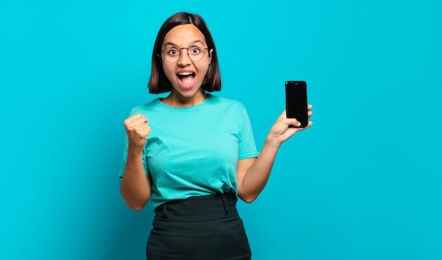 Młoda latynoska kobieta czuje się zszokowana, podekscytowana i szczęśliwa, śmiejąca się i świętująca sukces, mówiąc wow!