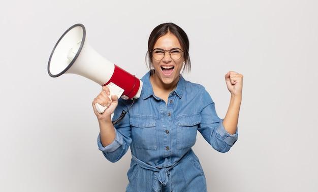 Młoda latynoska kobieta czuje się zszokowana, podekscytowana i szczęśliwa, śmieje się i świętuje sukces, mówiąc wow!