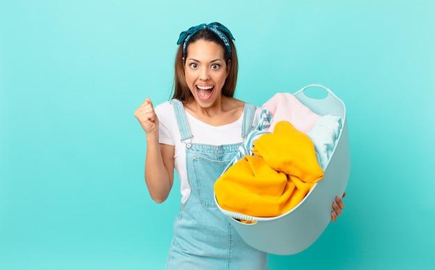Młoda latynoska kobieta czuje się zszokowana, śmieje się i świętuje sukces i myje ubrania