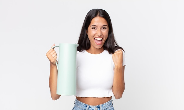 Młoda latynoska kobieta czuje się zszokowana, śmieje się i świętuje sukces i trzyma termos z kawą