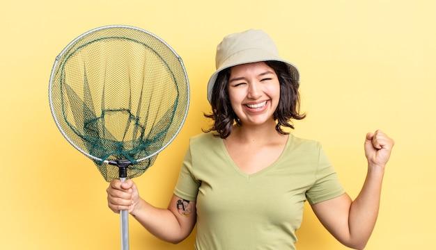 Młoda latynoska kobieta czuje się zszokowana, śmieje się i świętuje sukces. koncepcja sieci rybackiej