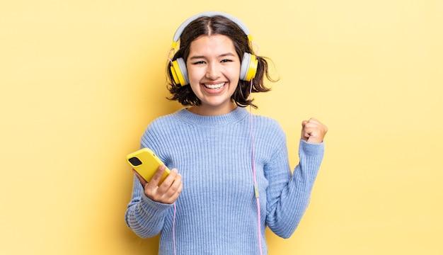 Młoda latynoska kobieta czuje się zszokowana, śmieje się i świętuje sukces. koncepcja słuchawek i smartfona